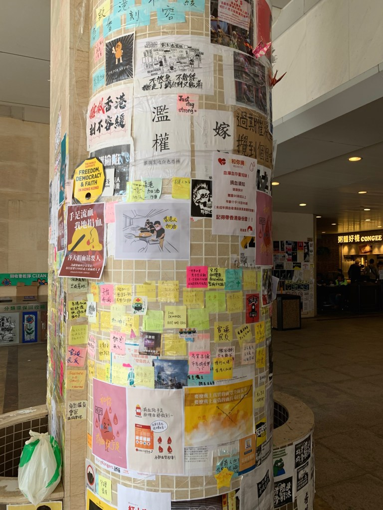 An architectural column in a hospital, covered in messages -- some are written on post-its, some are printed posters.