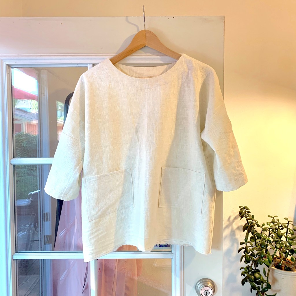cream linen boxy top hanging on a hanger on a French door