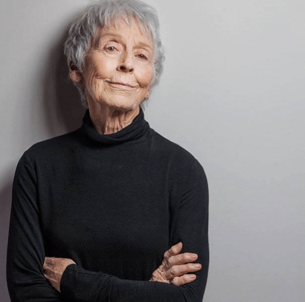 Grey hair woman smirking at the camera confidently