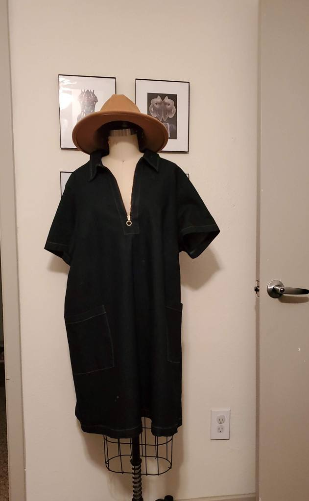 Dark denim nee-length tunic on a mannequin that has a hat instead of a head.