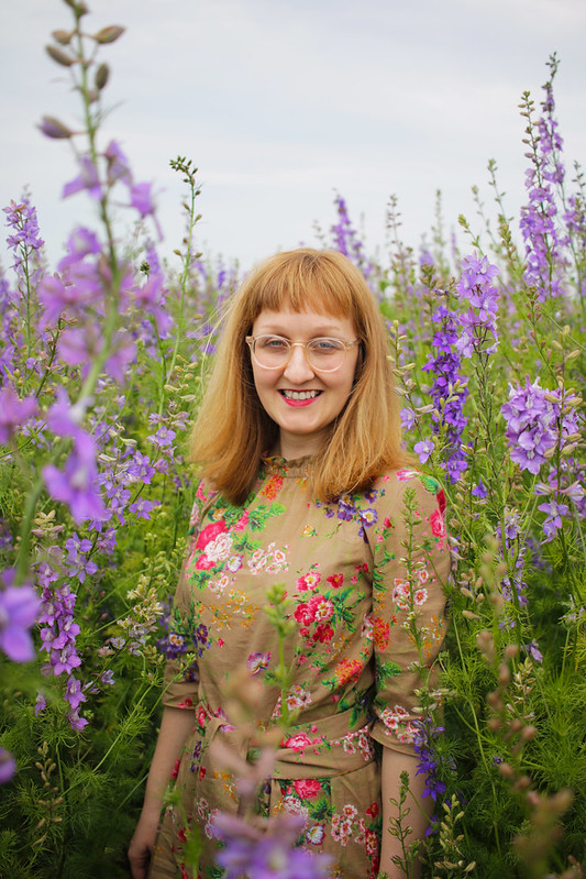 A picture of Charlotte standing in a field of tall, lilac flowers.  She is wearing a floral dress and glasses.  She is looking at the camera and smiling.