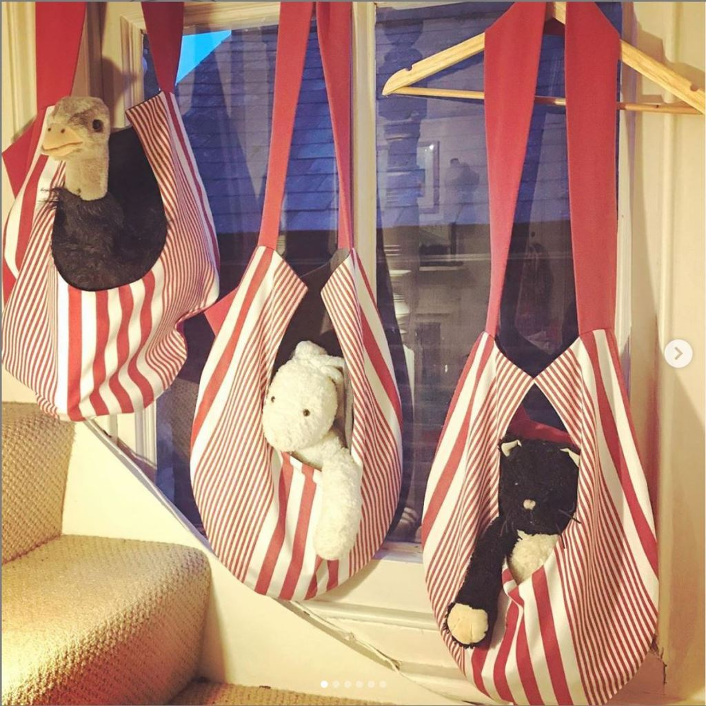Red and white striped hanging pouches with stuffed animals in them