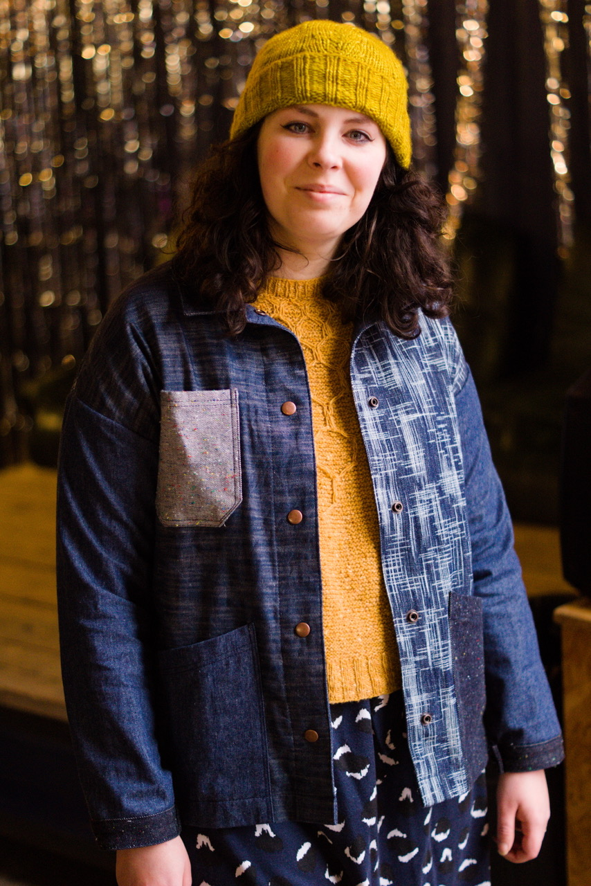 A white woman with brown hair is looking at the camera and smiling wearing a yellow hat and jumper and a denim jacket made from lots of different kinds of denim.