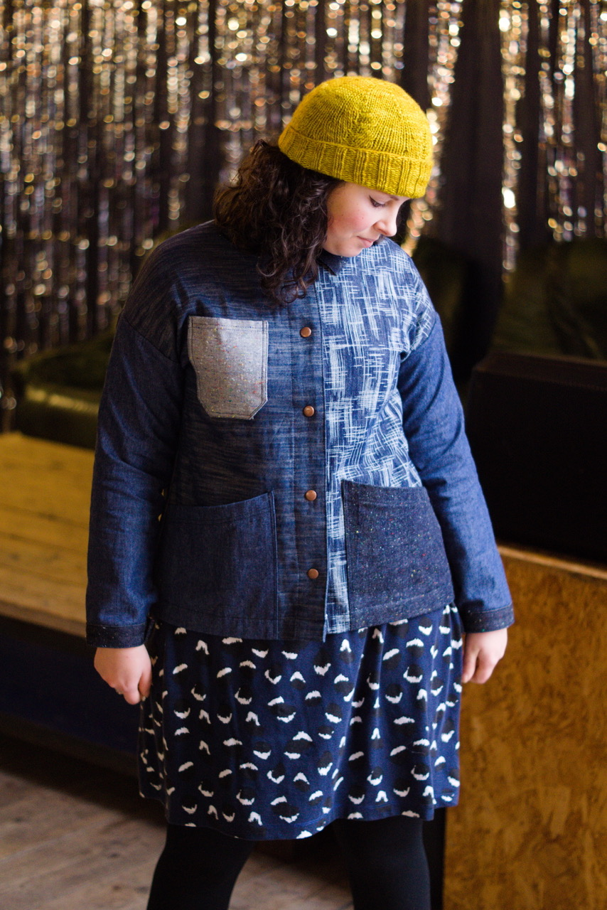 A white woman in a yellow knitted hat is looking down at the floor wearing a denim jacket made from lots of different kinds of denim.