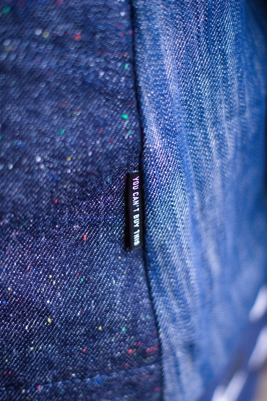 A close up of a label sewn into the denim jacket. It is a black label that says 'You Can't Buy This' in silver text.