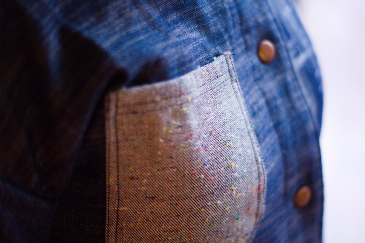 This photo shows a close up of a chest pocket on a blue denim jacket, it is a lighter colour and has red, green and yellow flecks of colour in the material.