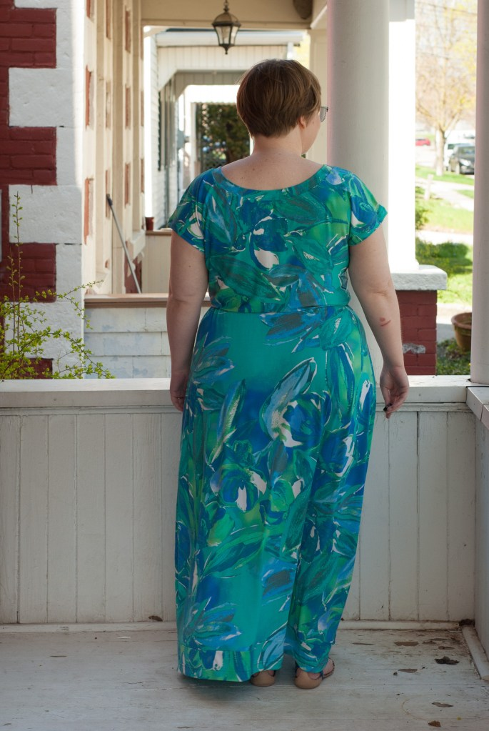 Blonde woman looks away from camera in a turquoise maxi dress, with a secret seam at the hem.