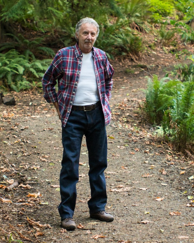 An older man stands outdoors on a dirt path surrounded by ferns and fallen leaves. He is wearing a pair of jeans, a red/white/blue plaid button-down shirt, a white t-shirt, and brown shoes.