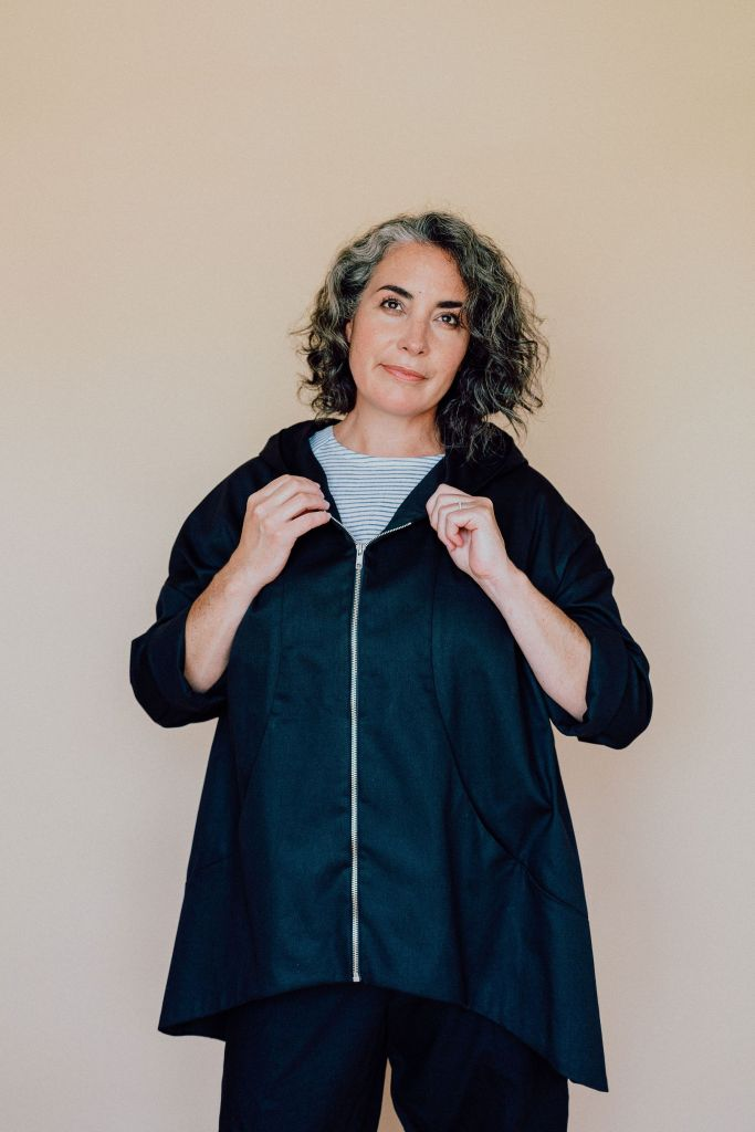 A woman models an In the Folds Hove jacket made in dark denim. Her hands hold the top of the zipper opening, and the open neckline reveals her narrow-striped top underneath. She is also wearing dark trousers.