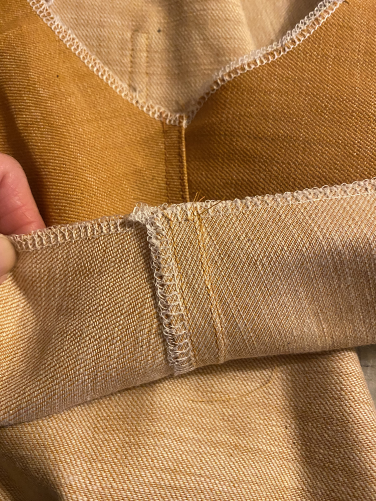 A piece of a goldenrod denim jacket is shown; the lower edge is turned back to reveal the wrong side of the fabric, and the underside of the seam finish. There are two rows of topstitching which match the color of the fabric, and the raw edges have been overlocked in white thread.