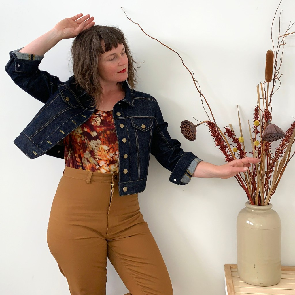 A young woman wears a denim jean jacket that she made using the Seamwork Audrey pattern. Her trousers are mustard and high-waisted, and she also wears a warm-toned floral top. Her right hand is held up at her head, swinging that side of the jacket open; her left touches a home decor display in a jug or vase that is next to her.