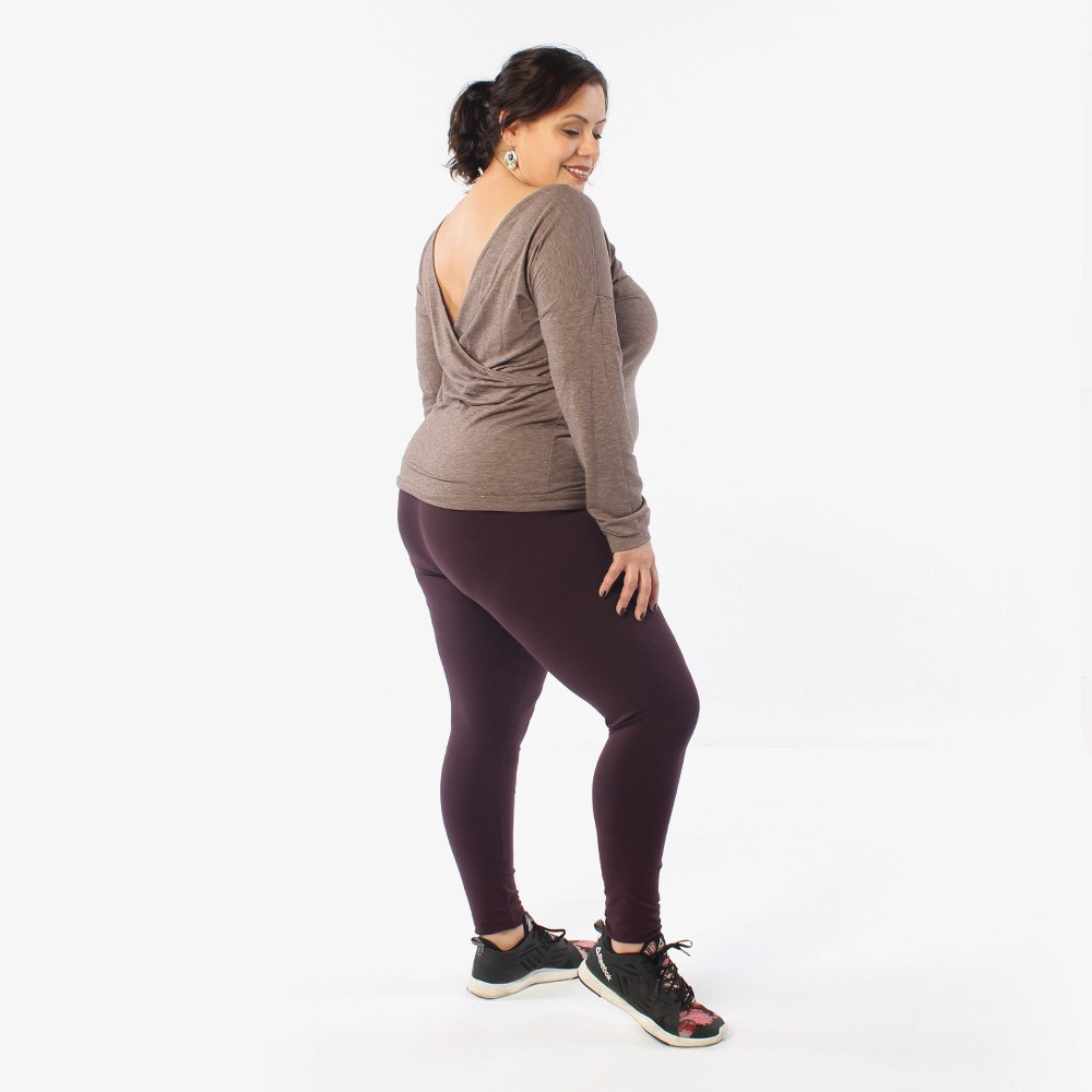 A model wears a pair of Helen's Closet Avery leggings in an aubergine knit. She wears a taupe knit top with a surplice back neckline and a pair of sneaker shoes. She is in profile to the camera, showing the no-side-seam design of the leggings.