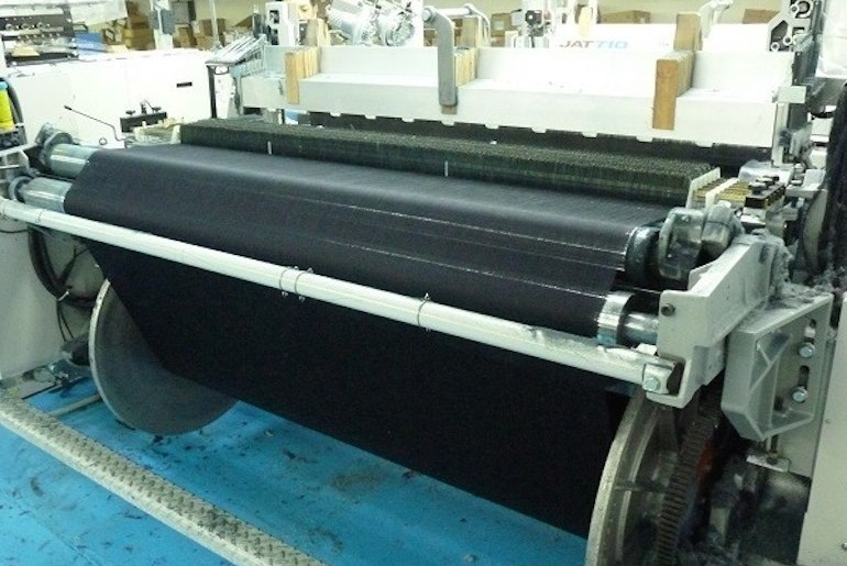 A projectile loom in a textile factory, with a roll of deep indigo denim being woven.