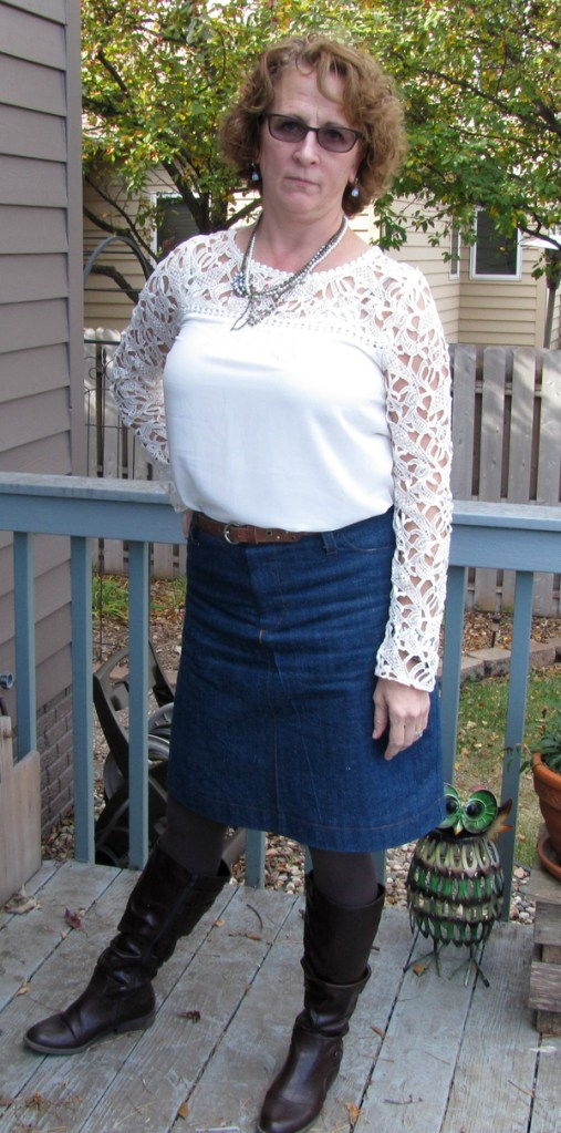 A woman stands on a deck, wearing her Style Arc Sally skirt that she has made in a denim. Her white top features lace sleeves and a yoke. She is also wearing gray tights and dark brown leather calf-high boots, as well as multiple coordinating necklaces. An adjacent house, a fence, and a tree can be seen behind her.