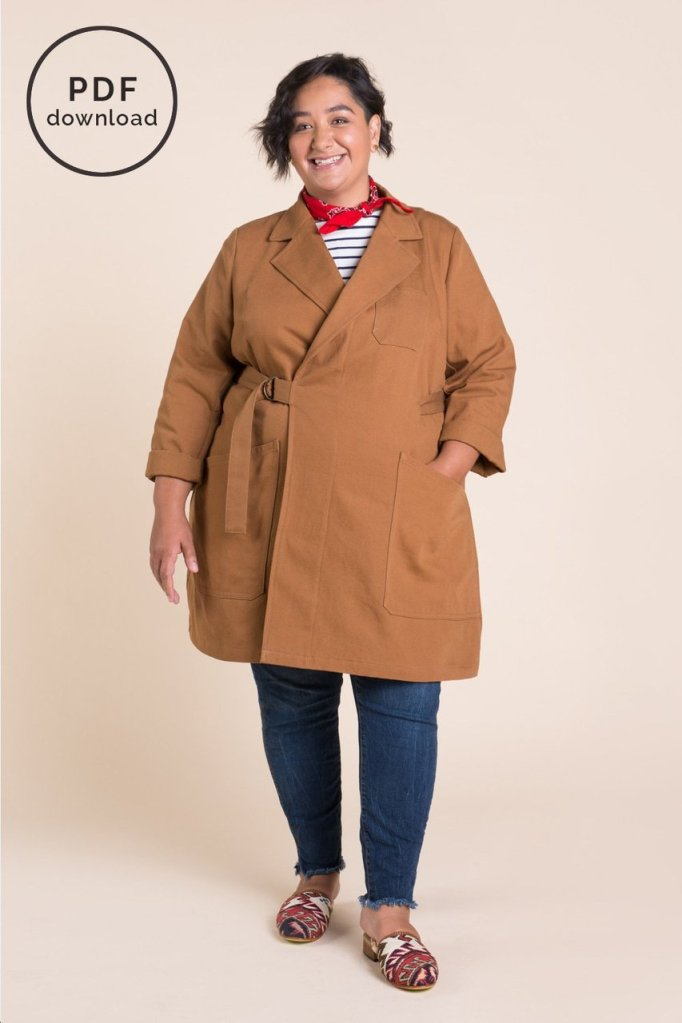 A model wears a Closet Case Patterns Sienna Maker Jacket in their newly-expanded size range. The jacket is a tobacco color, and features exterior pockets (upper and lower) and a d-ring belt to close. The model also wears blue jeans, a white and navy-striped top, and a red bandana neckerchief. Her left hand is placed in the lower jacket pocket, and she smiles at the camera.