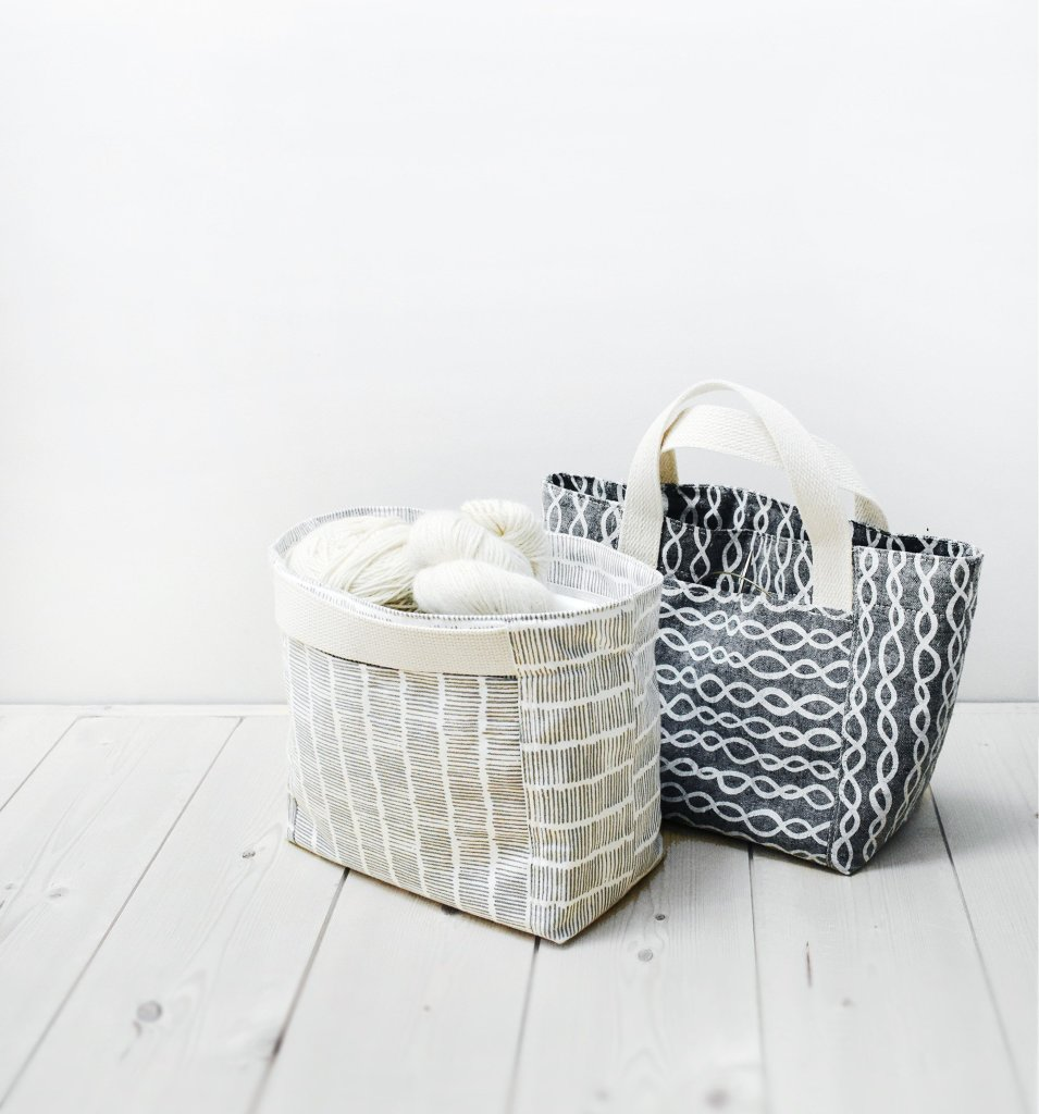 """Two Indigobird Designs Sierra totes sit on a white wood plank floor in front of a white wall. One bag has traditional """"loop"""" handles that are off-white in color; that bag is made of a charcoal gray fabric with a white """"chain"""" print. The second bag is narrower than the first and is a knitting project bag; it is sewn in a white and gray graphic print featuring rows of short lines, and the handles are flat against the face of the bag. Multiple skeins of ivory yarn can be seen resting inside."""