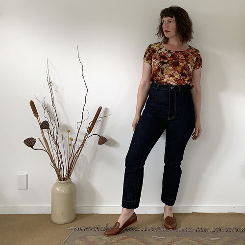 A young woman models her self-made pair of denim Philippa pants, which she has paired with cognac-colored leather shoes and a warm-toned floral tee.