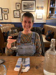 photo of Tricia in her new upcycled pinafore raising a glass of wine to the photographer