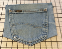 Unpicked right side jeans pocket on a gridded board