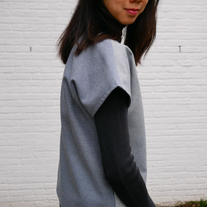 Side view of Kate wearing a loose denim top over a black turtleneck.  The side view clearly shows that the front of the denim top is a lighter color than the back.