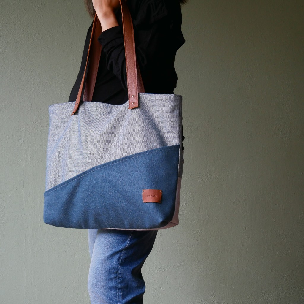 Kate holding a large tote bag made from two different colors of denim and leather accents