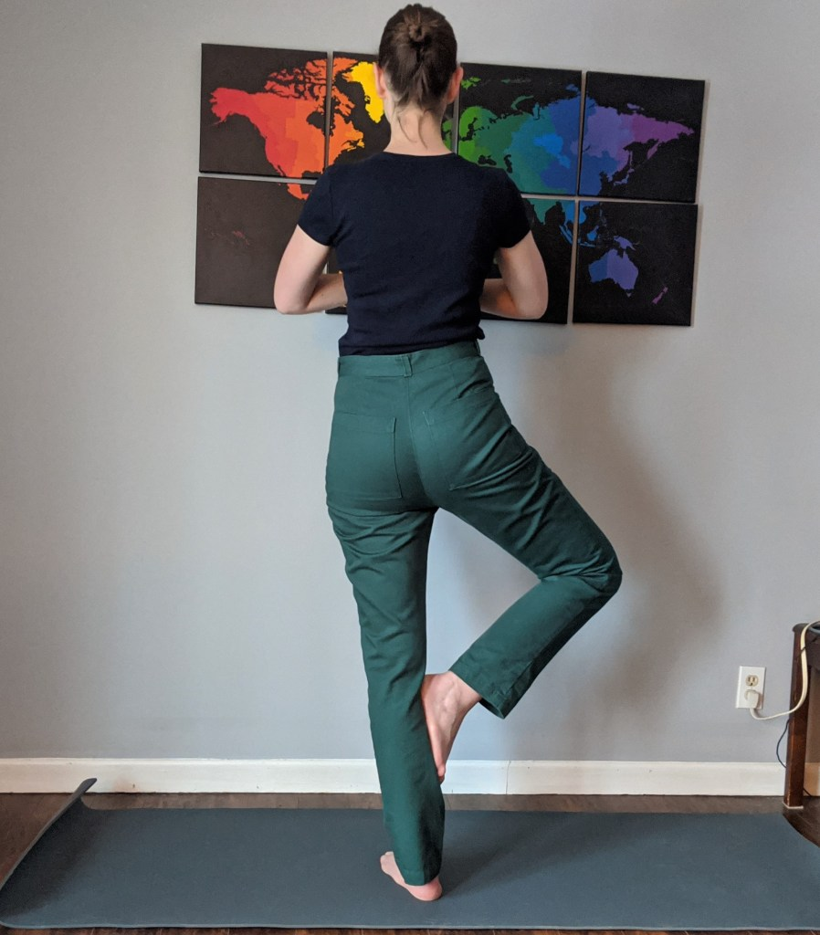 The author faces away from the camera, standing in tree yoga pose wearing Lander pants