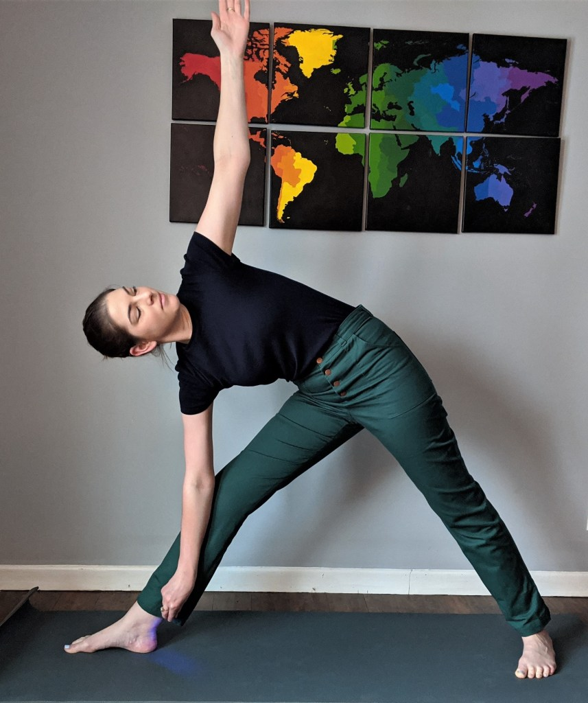The author stands in triangle yoga pose wearing Lander pants
