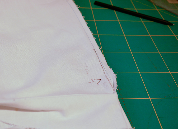 Some white fabric with a brown line going up from the seam to the waitline to show the adjustment needed