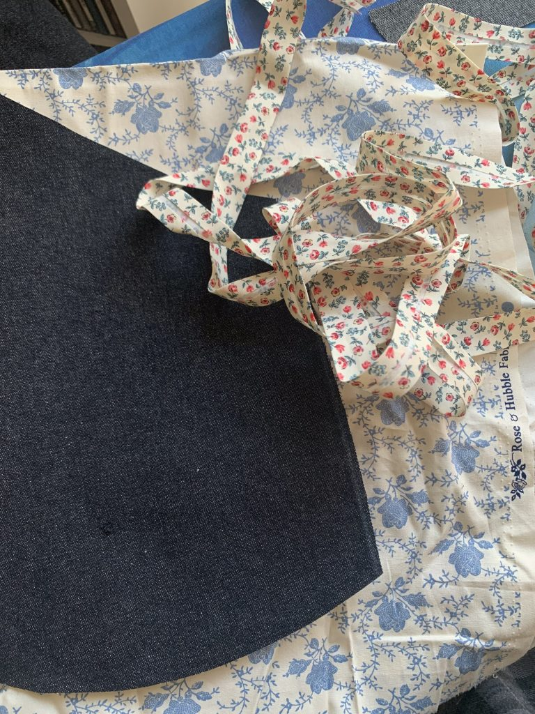 Denim fabric for the pinafore with floral cotton  from Sophy's mother's stash, and floral bias tape.