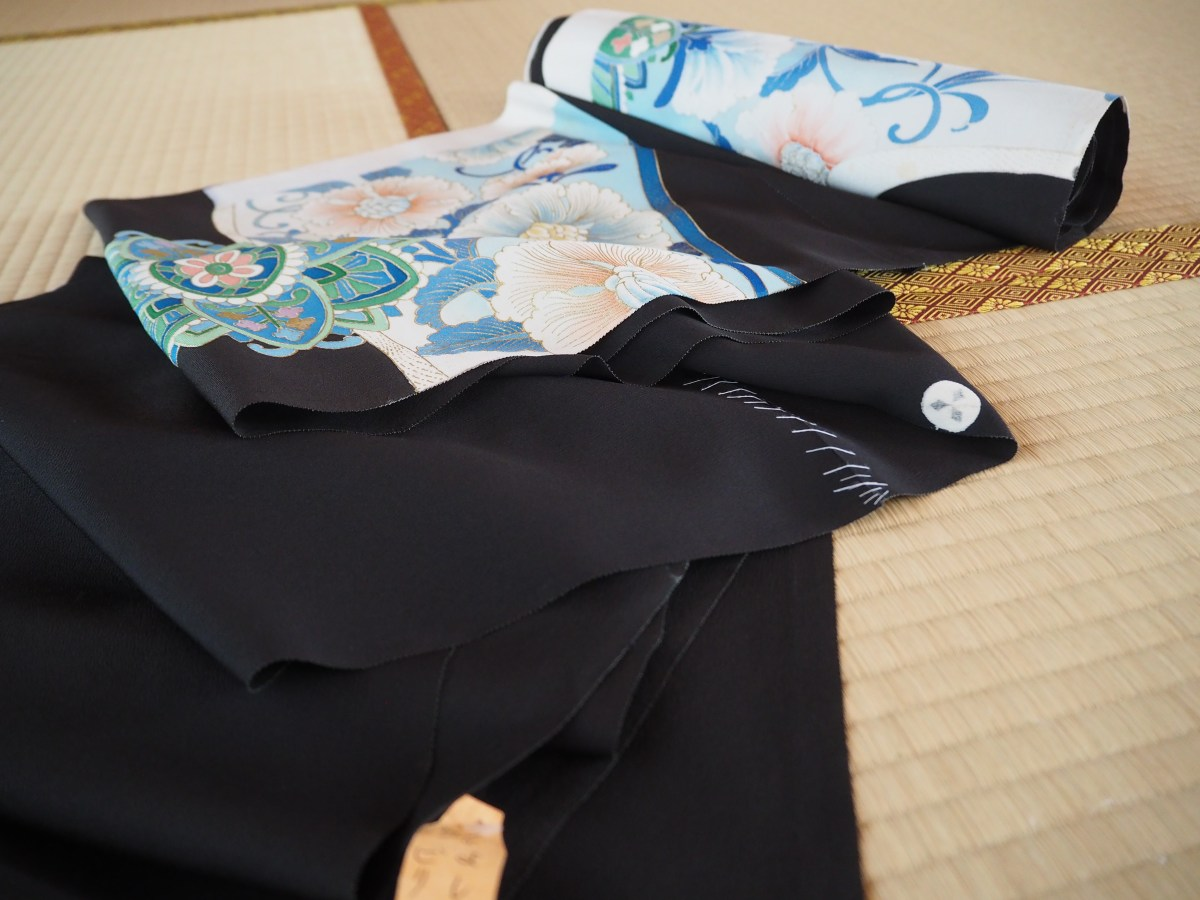 A black bolt of kimono fabric with yuzen paint sits on the tatami, basted together after washing.