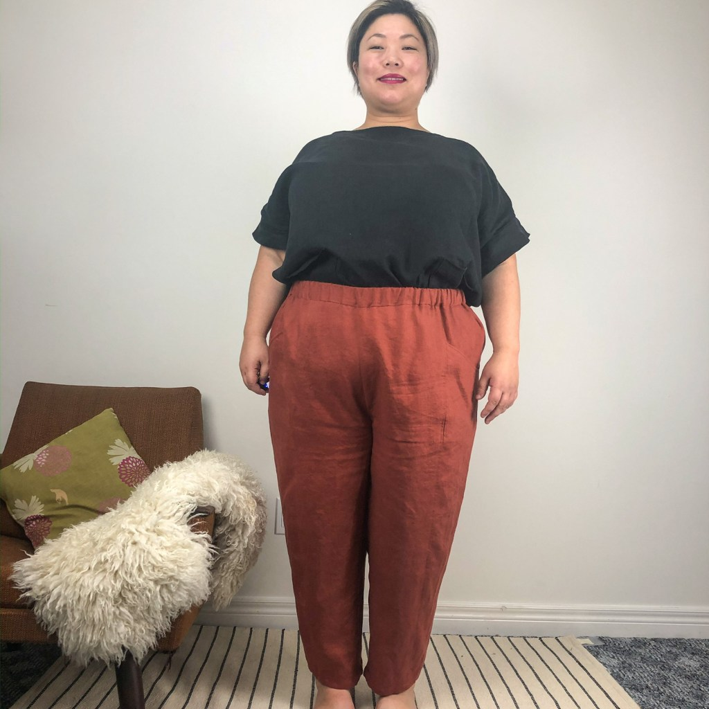 Leila shows off her Sculthorpe pants, which have a tapered leg and a gathered waist. She has a black top tucked into them to show the fit at the waist and hip.