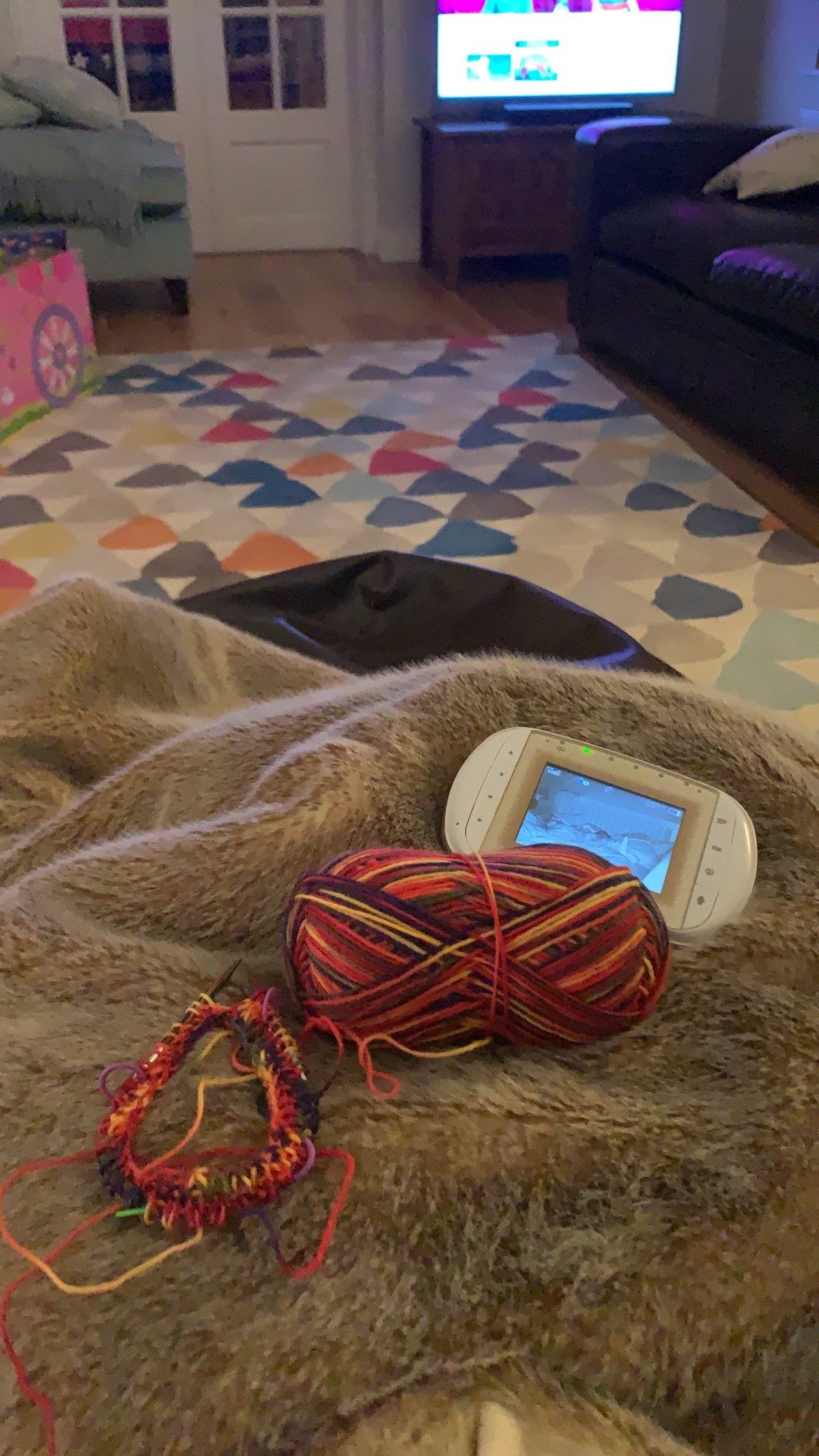 A colourful skein of sock weight yarn is on a fluffy throw. Some of the yarn has been worked in rib stitch on a circular needle. A monitor lies next to the yarn and the TV is on in the background.