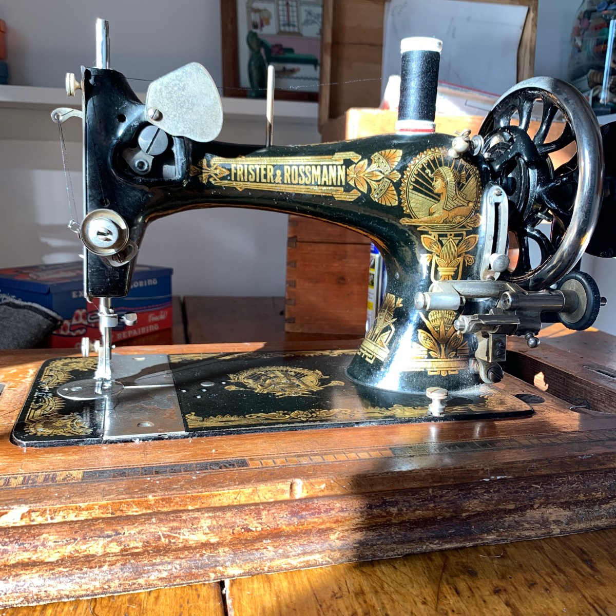 A Frister & Rossman vintage hand crank sewing machine sits on a table.