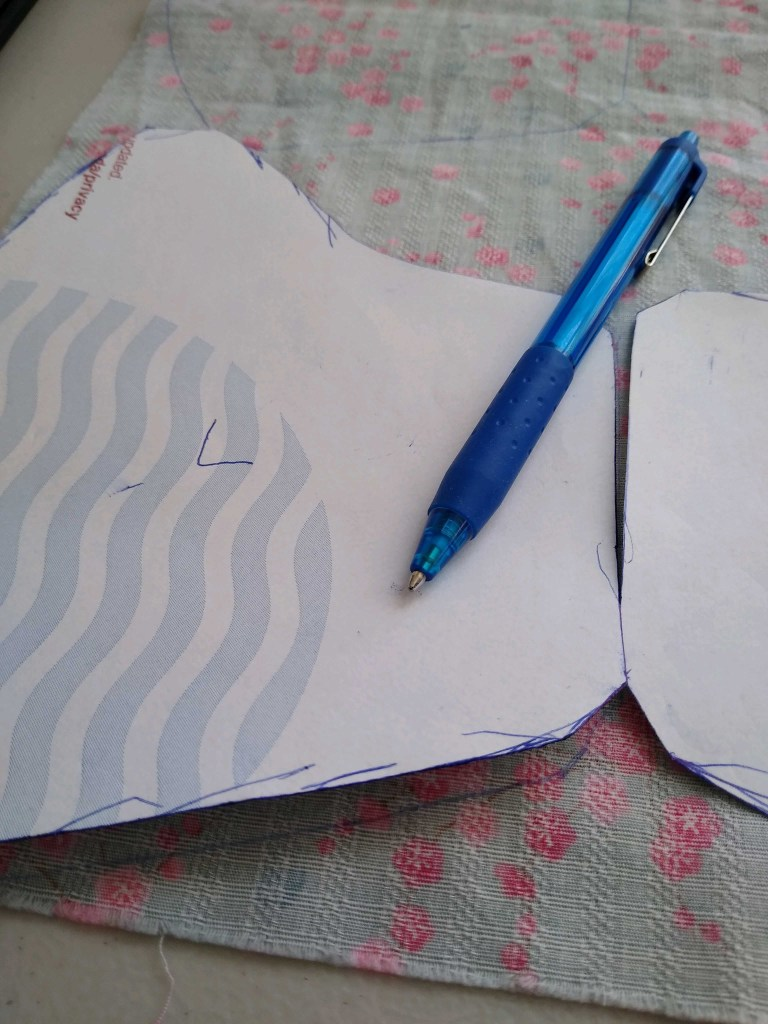 Image of a blue pen on top of pattern pieces that have been traced onto fabric with blue ink.
