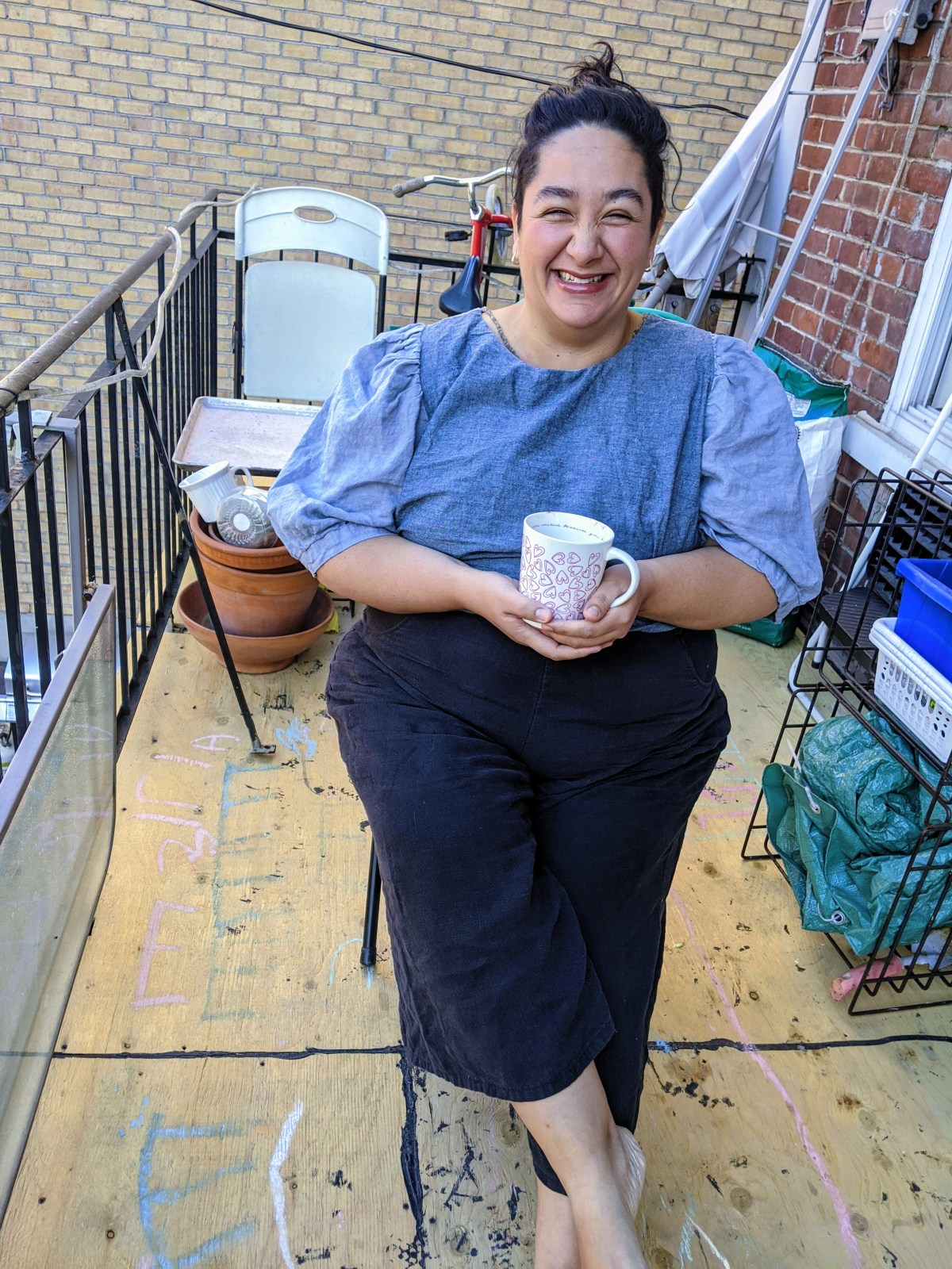 The author in a blue blouse and dark pants, smiling at the camera and holding a mug outdoors