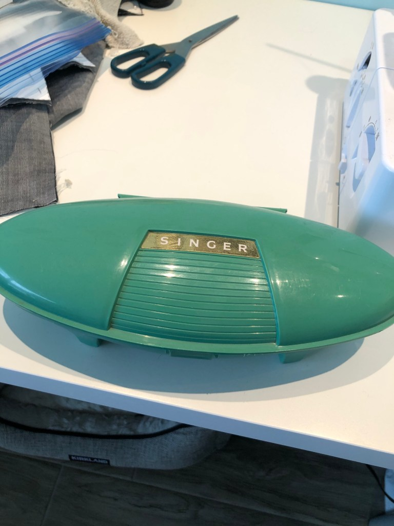 The clamshell case for Kerry's vintage Singer buttonholer. It's classic retro grey-green, in an elongated oval bubble. The case sits on Kerry's sewing table with a pair of Ikea scissors that she swears she didn't use to cut fabric!