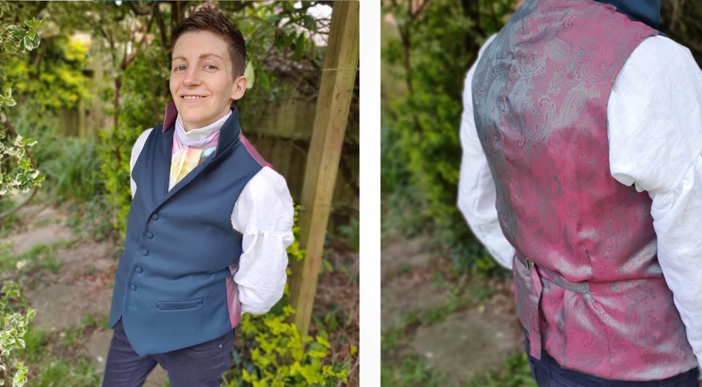 Emery wearing a linen regency-style shirt, a teal collared waistcoat and a rainbow dyed linen cravat.