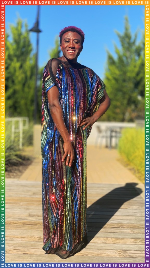 Terrance wears a rainbow sequin caftan dress and is smiling at the camera. The picture has a border reading 'Love is Love'