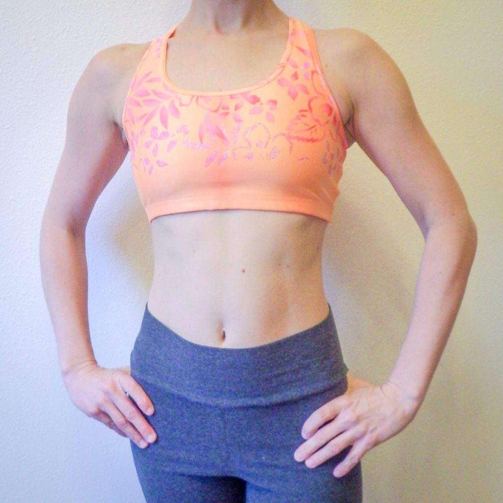 Person modeling an orange sports bra with gray leggings