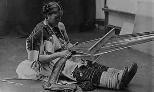 A black and white image depicts a Two Spirit or Nádleehi person wearing traditional dress sitting with a musical instrument.