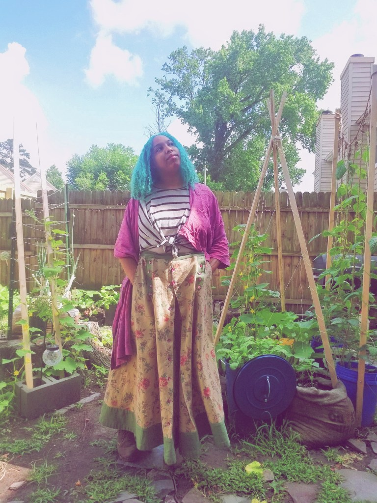 Whitney stands in a garden, wearing a full floral skirt from a historic costume, with a striped wrap tee and a magenta wrap over top. Her skirt has pockets!