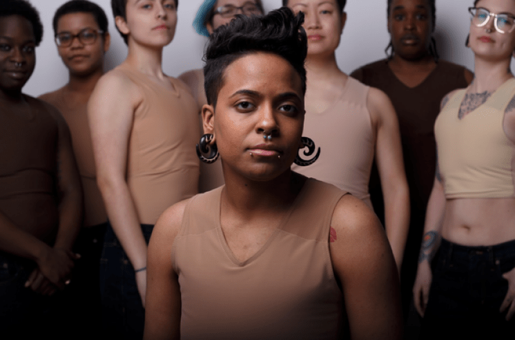 One person sits to the foreground, they have brown skin, short black hair and piercings. They are modelling a chest binder. Several people of different ethnic backgrounds stand behind modelling their chest binders.