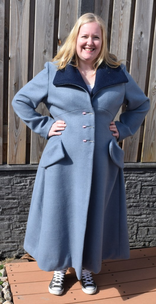 Marijke is standing in front of a wooden fence. She is wearing a light blue ankle-length coat with darker blue collar facing.  She has her hands on her hips and is looking at the camera and smiling.