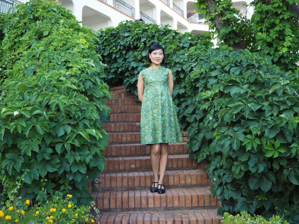 Karina is standing on a set of brick steps with green leafy plants either side of the stairs.  She is wearing a short green floral dress and dark coloured shoes. She is looking at the camera and smiling.