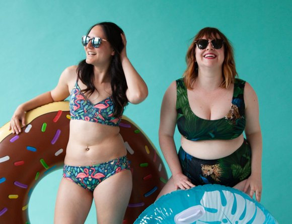 Two women wearing two-piece swimsuits and sunglasses are smiling and holding inflated water rafts.