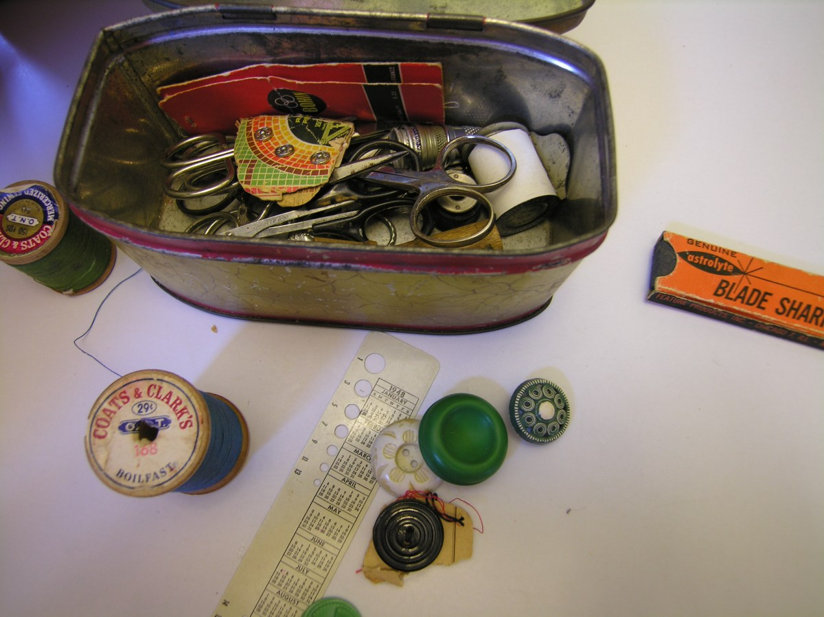 Photo of a metal box with a hinged lid. The box's lid has been lifted, and in the box are vintage sewing notions, such as small scissors. There are some notions outside of the box; for example, two vintage Coats and Clark's thread spools and a few buttons.