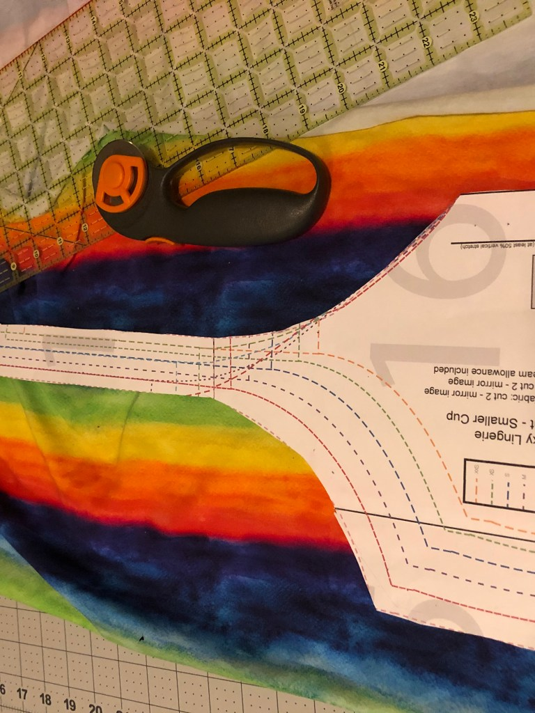 Part of a sewing pattern piece, showing adjustable seam lines for different sizes, lays atop a lovely hand-painted look fabric, with wide bands in the colours of the rainbow.