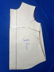 The pattern piece with blue marker lines, now with an orange marker line showing the intended reduction of the armscye. There is also an additional piece of paper taped along the side seam, with an orange marker line marking a slight reduction in the curve along the waist.