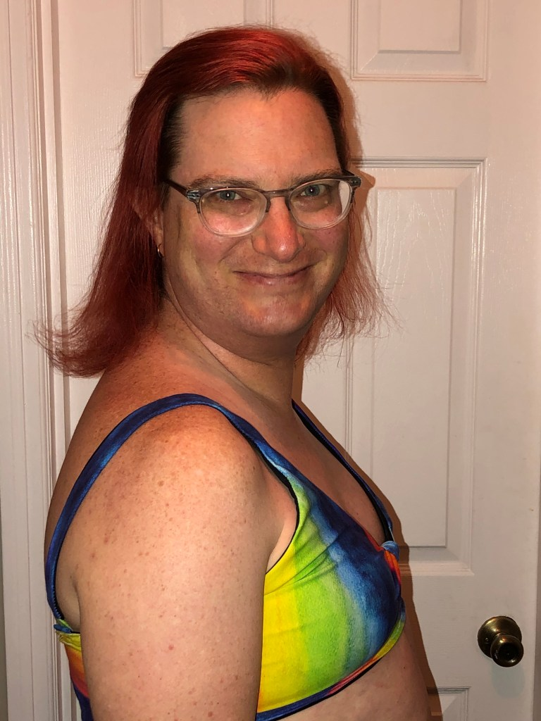 A smiling woman, with glasses shows off her rainbow-hued Lucky Bra. It fits her really well!