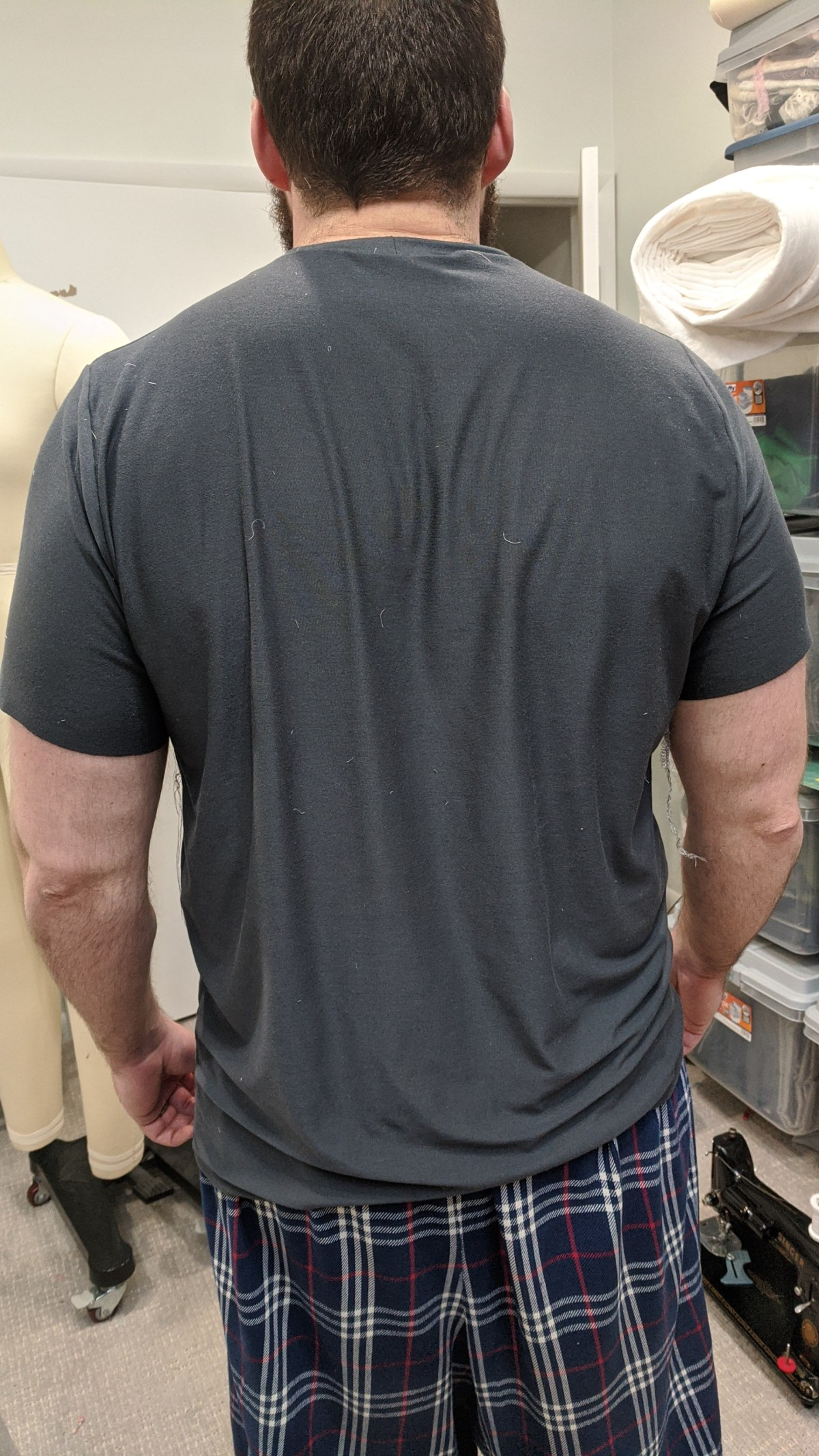 A photo of the author's husband from the back, wearing the first muslin of a dark-coloured tee shirt.